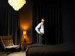 Man in glasses standing in bedroom