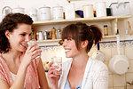 Smiling women drinking water in kitchen