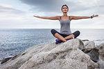 Woman meditating on boulder