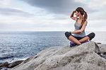 Woman overlooking ocean on boulder