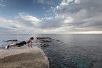 Woman on boulder overlooking ocean