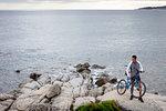 Man holding bicycle on boulder