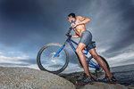 Man pushing bicycle on boulder