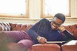 Young man enjoying reading on sofa