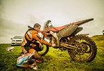 Teenage boy checking motorcycle at motocross