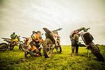 Three boys checking motorcycles at motocross