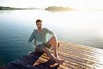 Portrait of mature man sitting on decking by lake, Munich, Germany
