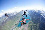 Team of three skydivers in formation over Interlaken, Berne, Switzerland