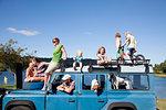 Family friends on top of off road vehicle, Lake Okareka, New Zealand