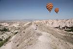 Female tourist and hot air balloons in rock formation landscape, Cappadocia, Anatolia,Turkey