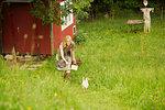 Woman in field chasing hen