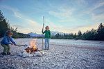 Boys poking campfire with sticks, Wallgau, Bavaria, Germany