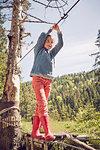 Young girl walking across single rope bridge