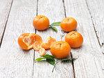 Mandarins peeled and whole on whitewashed wooden table
