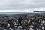 Mid adult woman standing on rocky coastline, looking away, Iceland