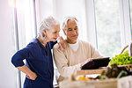 Senior couple browsing digital tablet recipes at kitchen counter