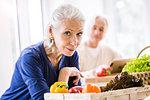 Portrait of senior woman preparing food at kitchen counter