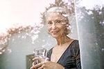 View through window of senior woman holding tumbler looking at camera smiling