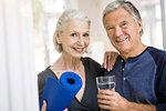 Senior man and woman holding yoga mat and tumbler of water looking at camera smiling