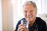 Portrait of senior man holding tumbler of water looking at camera smiling