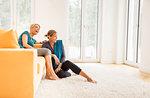 Two mature women taking an exercise break on living room sofa