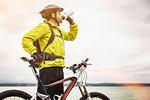 Mature male mountain biker drinking water at lakeside