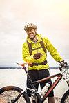 Portrait of mature male mountain biker at lakeside