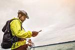 Male mountain biker reading map at lakeside