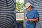 Farmer using cell phone by silos