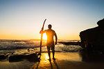 Man holding surfboard on rocky beach