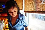 Woman wearing blue shirt, looking down