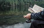 Man fishing with book, Buntzen Lake, British Columbia, Canada