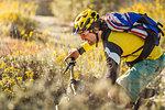 Young man mountain biking, Fontana, California, USA
