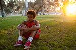 Sad looking boy sitting in park