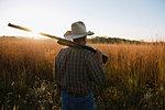Senior male farmer with shotgun on shoulder in remote field at dusk, Plattsburg, Missouri, USA