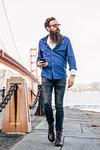 Man with beard checking smartphone at Golden Gate Bridge, San Francisco, California, USA
