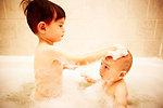 Boy bathing brother in bathtub