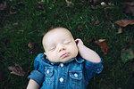 Baby boy wearing denim shirt lying on autumn leaf covered grass eyes closed
