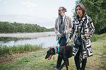 Couple walking dog by lake