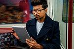 Businessman using digital tablet inside train
