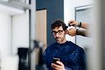 Male hairstylist cutting male customer's hair in hair salon