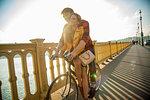 Couple crossing bridge on bicycle, Budapest, Hungary