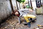 Boy falling off skateboard on street