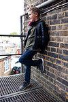 Boy leaning against brickwall