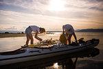 Two female kayakers preparing kayak, Quadra Island, Campbell River, Canada