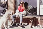 Young woman with pet dog at shopfront