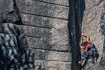 Young female rock climber climbing rock face, Smoke Bluffs, Squamish, British Columbia, Canada