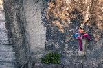 Young female rock climber climbing rock face, high angle view, Smoke Bluffs, Squamish, British Columbia, Canada