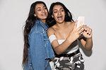Teenage twin sisters taking selfie with smart phone