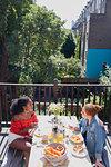 Young women friends enjoying brunch on sunny urban apartment balcony